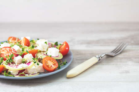 Healthy delicious tasty salad with tomatoes, radishes, cheeses, sprouts and sesame in plate on light wooden table, shallow depth of the field.