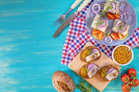 Sandwich with pieces of marinated herring with red onion and french mustard, decorated lemon and rosemary. Close up, restaurant serving, turquoise wooden surface, copy space, top view. Stock Photo