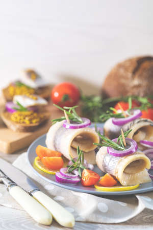 Delicious rolled herring fillet with red onion, cherry tomatoes, lemon and rosemary. Close up, restaurant serving, light gray wooden surface, copy space. Stock Photo