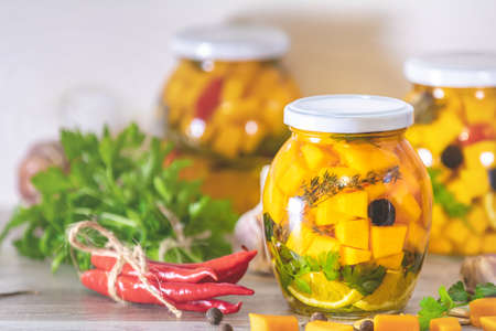 Marinated preserving jars. Homemade orange cut pumpkin pickles with red hot chili peppers, fresh parsley, spices on light gray wooden background. Fermented food.