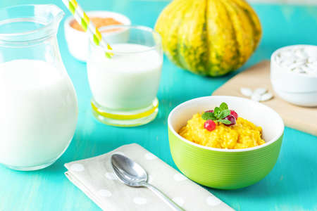 Pumpkin porridge. Delicious, homemade, pumpkin porridge with cranberry and mint in a white green plate on the table, ready to eat with milk. Blue turquoise table. Family breakfast. Free space for text, copy space. Stock Photo