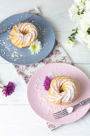 Delicious cakes with coconut chips on pink and gray plate on white table, autumn chrysanthemum. Family breakfast. Free space for text, copy space.