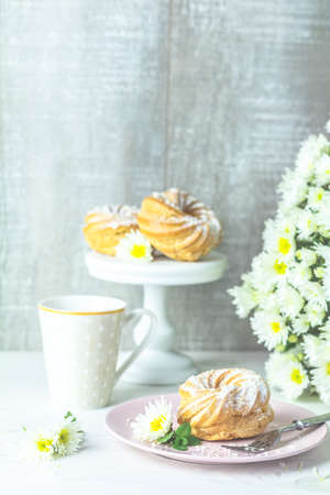 Delicious cake with coconut chips on pink  plate on white table, autumn white chrysanthemum and cup of coffee. Family breakfast. Free space for text, copy space. Stock Photo