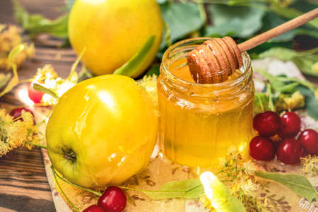 Open glass jar of liquid honey and honey dipper, bunch of linden flowers and red cherry on wooden surface. Ray of sunlight. Dark rustic style. Symbols of Jewish New Year - Rosh Hashanah Stock Photo