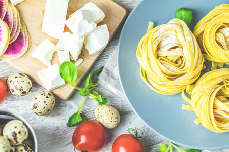 Raw homemade Italian typical pasta linguine noodles on plate, quail eggs, green lettuce, tomatoes, french mustard, feta cheese. Close up, top view.