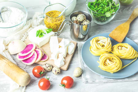 Raw homemade Italian typical pasta linguine noodles on plate, quail eggs, green lettuce, tomatoes, french mustard, feta cheese, sliced red radishes and flour on light table. Shallow depth of the field