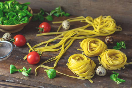Raw homemade Italian typical pasta linguine noodles, quail eggs, green lettuce, tomatoes and flour on dark wooden table. Shallow depth of the field, close up, copy space.