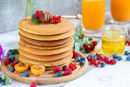 Fresh delicious pancakes with summer raspberries, blueberries, red currants, apricot, peach and mint. Two glasses of orange juice, honey, light background. Sweet nutritious food.