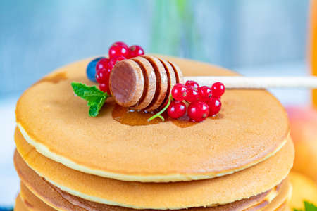 Fresh delicious pancakes with summer raspberries, blueberries, red currants, apricot, peach, mint and and honey dipper close up. Sweet nutritious food. Shallow depth of the field. Banque d'images
