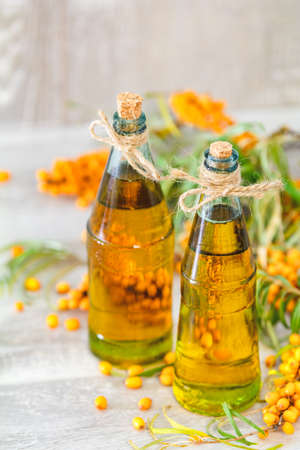Natural organic sea-buckthorn berry and sea buckthorn oil in glass vintage bottle on gray wooden background. Dark rustic style, natural remedy.