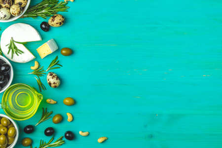 Set of cheese camembert, black and green olives, quail eggs on plates, olive oil and rosemary, on a blue turquoise wooden table background. Top view, copy space.