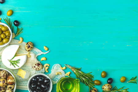Cheese camembert, black and green olives, quail eggs on plates, olive oil and rosemary, on a blue turquoise wooden table background. Top view, copy space. Фото со стока