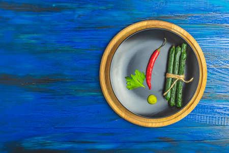 Kabanosy, sausages green with wasabi made of pork in plate on a dark blue wood surface with addition of fresh herbs, chili pepper and spices Stock Photo