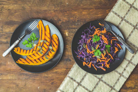 Grilled sliced pumpkin with parsley and pumpkin seeds, salad of purple cabbage, carrots and seeds in black ceramic plates on dark old wooden surface, top view, copy spice.