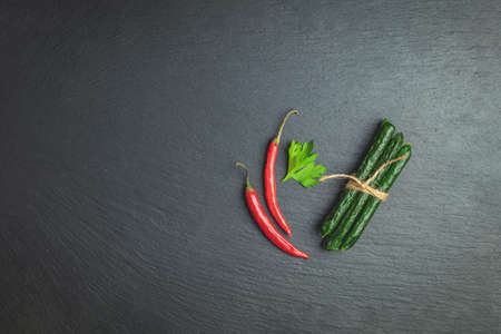 Kabanosy, sausages green with wasabi made of pork on a black wood stone surface with addition of fresh herbs, chili pepper and spices Stock Photo