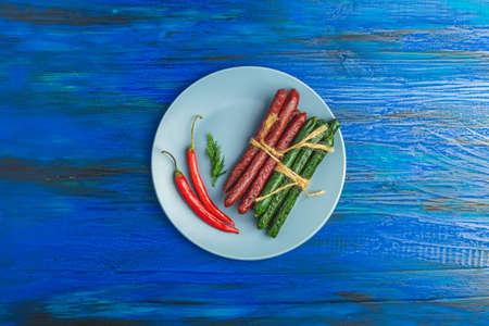 Kabanosy, sausages green with wasabi made of pork in black plate and traditional polish in gray plate on a dark blue wood surface with addition of fresh herbs, chili pepper and spices.