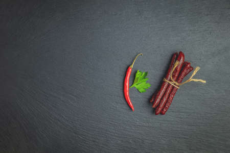 Kabanosy, sausages traditional polish made of pork on a black wood stone surface with addition of fresh herbs, chili pepper and spices