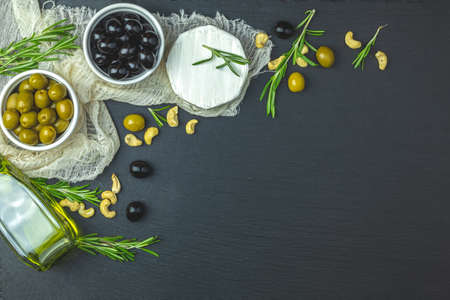 Set of cheese camembert, black and green olives, quail eggs on plates, olive oil and rosemary, on a black stone table background. Top view, copy space. Stock Photo