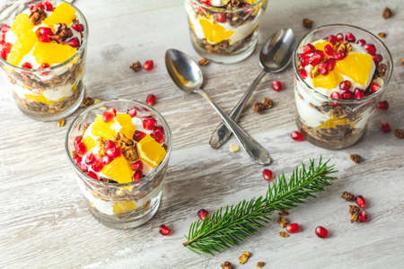 Greek yogurt with granola, orange and pomegranate berries for healthy breakfast on light gray wooden table, copy space, shallow depth of the field.