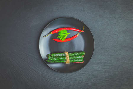 Kabanosy, sausages traditional polish and green with wasabi made of pork in plate on a black stone surface with addition of fresh herbs, chili pepper and spices Stock Photo