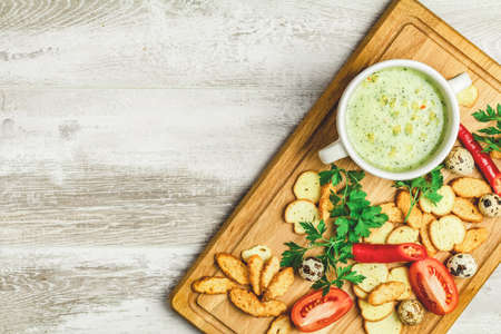 Concept of healthy vegetable and legume soups. Vegetables soup with carrot, eggs and chicken, mushroom cream soup with herbs and crackers and ingredients. Top view on the background of a light gray wooden board, copy space.