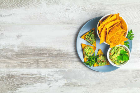 Guacamole and nachos with ingredients on the background of a light gray wooden board. Top view, copy space.