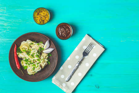 Tasty homemade meat dumplings or traditional italian ravioli of wholemeal flour sprinkled with fresh parsley on plate on blue turquoise table surface, copy space, view from above. Stock Photo