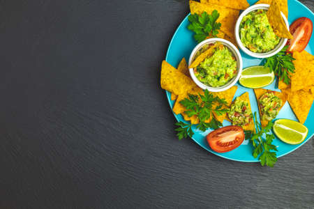Guacamole and nachos with ingredients on the background of a black stone board. Top view, copy space.