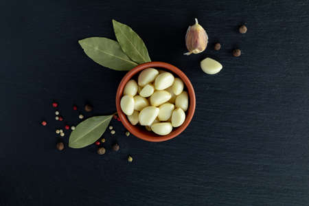 Fresh garlic heads, cloves set on a black stone surface, top view, copy space, copy space for text. Stock Photo