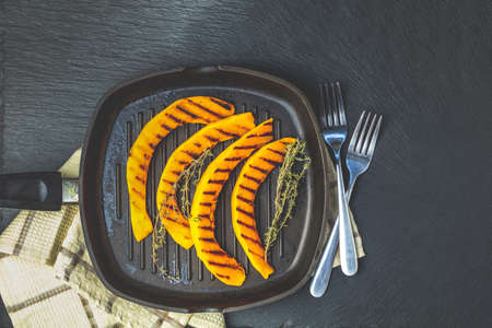 Grilled sliced pumpkin with thyme in dark frying pan on blackstone surface, top view, copy spice.