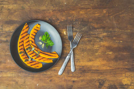 Grilled sliced pumpkin with parsley and pumpkin seeds in black ceramic plate on dark old wooden surface, top view, copy spice.