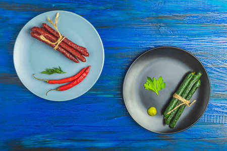 Kabanosy, sausages green with wasabi made of pork in black plate and traditional polish in gray and black plates on a dark blue wood surface with addition of fresh herbs, chili pepper and spices.