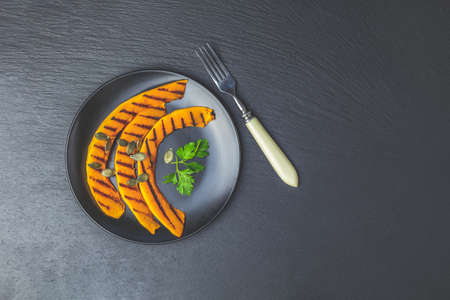 Grilled sliced pumpkin with parsley and seeds in black ceramic plate on blackstone surface, top view, copy spice.