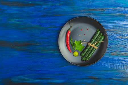 Kabanosy, sausages green with wasabi made of pork in black plate on a dark blue wood surface with addition of fresh herbs, chili pepper and spices