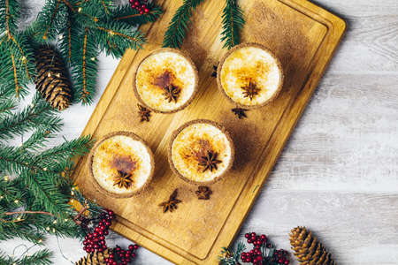 Eggnog with cinnamon and nutmeg for Christmas and winter holidays. Homemade eggnog in glasses with spicy rim. Top view, copy space.