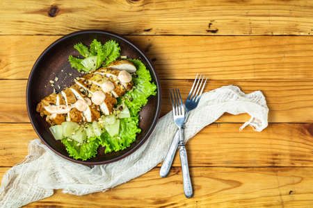 Delicious salad, chicken with pineapple, lettuce, cream sauce and walnut in ceramic plate on wooden surface, top view, copy space, hawaiian, asian food