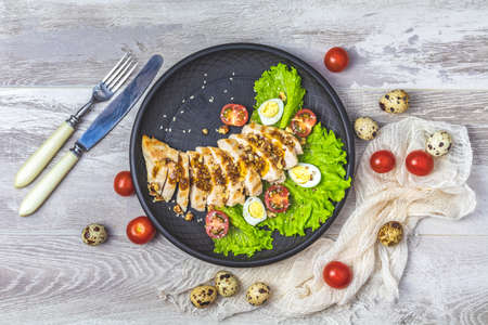 Delicious salad, chicken with honey and mustard souse, lettuce, quail eggs, cherry tomatoes and sesame in black ceramic plate, light gray wooden surface, top view, copy space, hawaiian, asian food