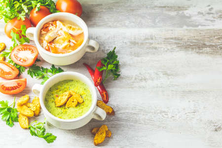 Concept of healthy vegetable and legume soups. Vegetables soup with carrot, eggs and chicken, mushroom cream soup with herbs and crackers and ingredients. Background of a light gray board, copy space