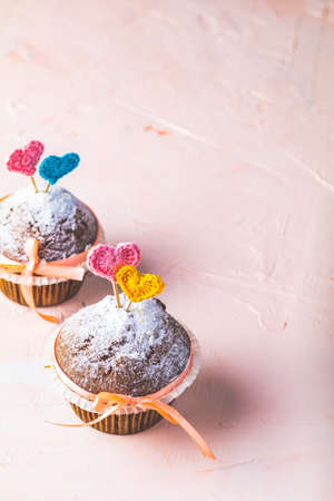 Tasty delicious homemade muffin on light pink living coral stone concrete surface with knitting hearts, copy space. Sweet food for valentines day.