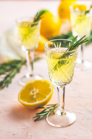 Traditional italian homemade lemon alcohol drink liqueur limoncello with pieces of lemon and rosemary herb on light pink living coral stone concrete surface Stock Photo - 115558173