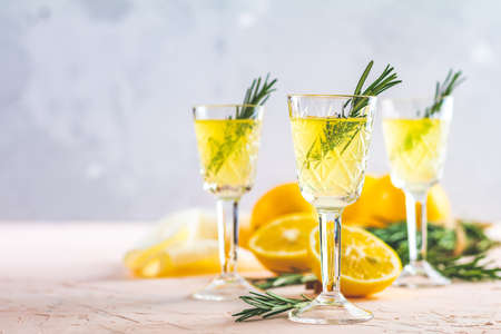 Traditional italian homemade lemon alcohol drink liqueur limoncello with pieces of lemon and rosemary herb on light pink living coral stone concrete surface