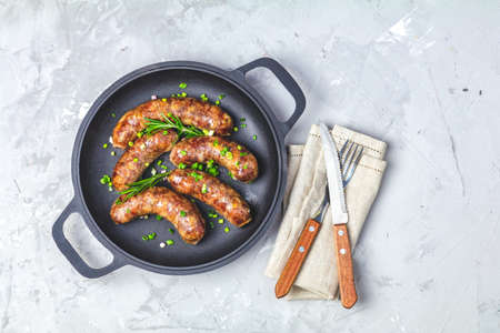 Fried sausage in a frying pan with herbs and spices with knife and fork, green onion, parsley and rosemary on light gray concrete surface background, top view, free space for your text.