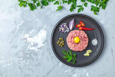 Steak tartare with yolk and ingredients on black ceramic plate, set of cutlery knife and fork on light gray stone concrete textured surface background. Copy space background, top view flat lay.