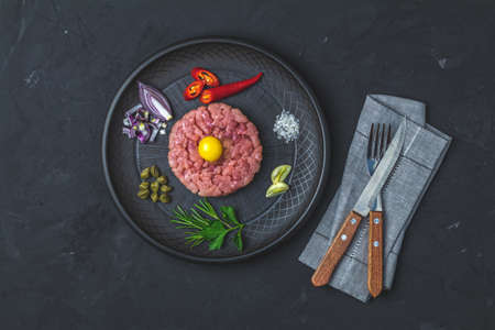 Steak tartare with yolk and ingredients on black ceramic plate, set of cutlery knife and fork on black stone concrete textured surface background. Copy space background, top view flat lay. Stock fotó