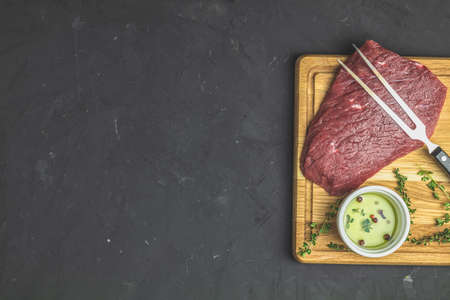 Fresh raw meat beef steak on wooden cutting board with ingredients for cooking spices, thyme, rosemary and olive oil, dark background, top view, copy space for you text. Stock Photo
