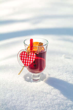 Cup with delicious mulled wine and spices on a snow covered background decorated with heart. Beautiful sunny winter  day, Valentines Day greeting card with copy space for you text.