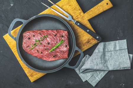 Fresh raw meat beef steak with ingredients for cooking spices, thyme and rosemary in black frying pan on dark background, top view, copy space for you text. Stock Photo