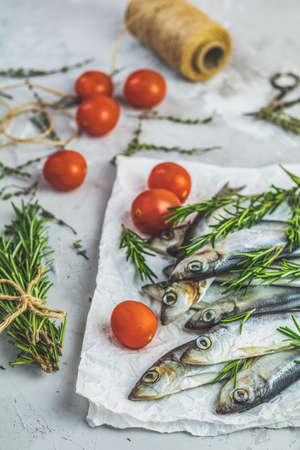 Sardines or baltic herring with tomatoes and rosemary on paper on light gray concrete table surface. Raw uncooked sea fish. Copy spice.