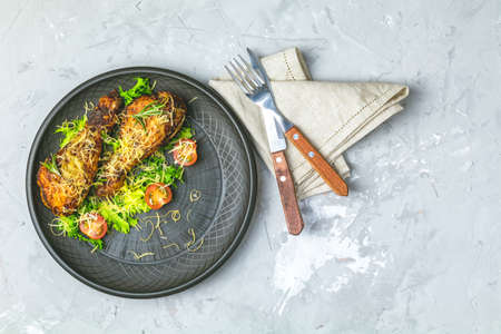 Baked chicken drumstick in a black ceramic plate with tomatoes and rosemary, light gray stone concrete surface, top view, copy space. Stock Photo