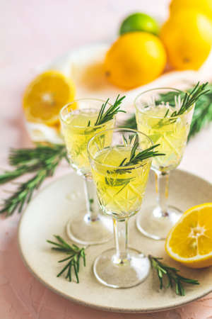 Traditional italian homemade lemon alcohol drink liqueur limoncello with pieces of lemon and rosemary herb on light pink, peach or coral color stone concrete surface Stock Photo